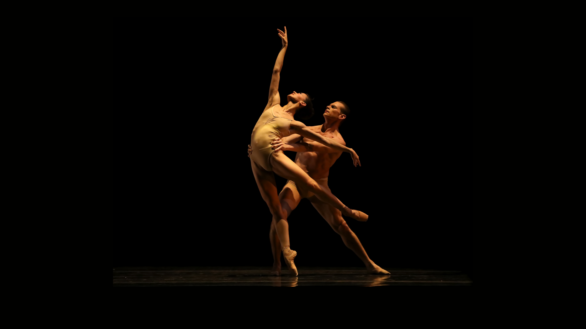 One male and one female dancer in a spotlight on a dark stage.