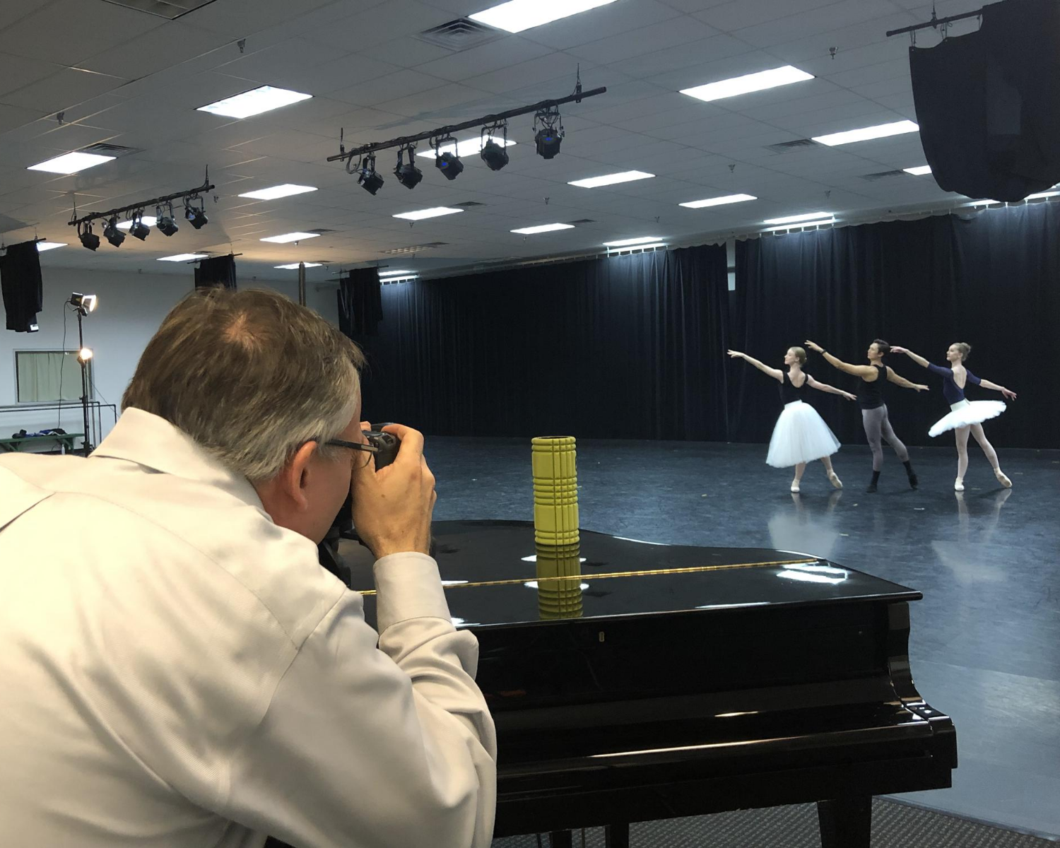 Photographer shooting photos of 3 dancers in arabesque, 2 female and 1 male.