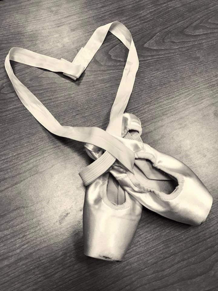 Two pointe shoes positioned with ribbons creating a heart