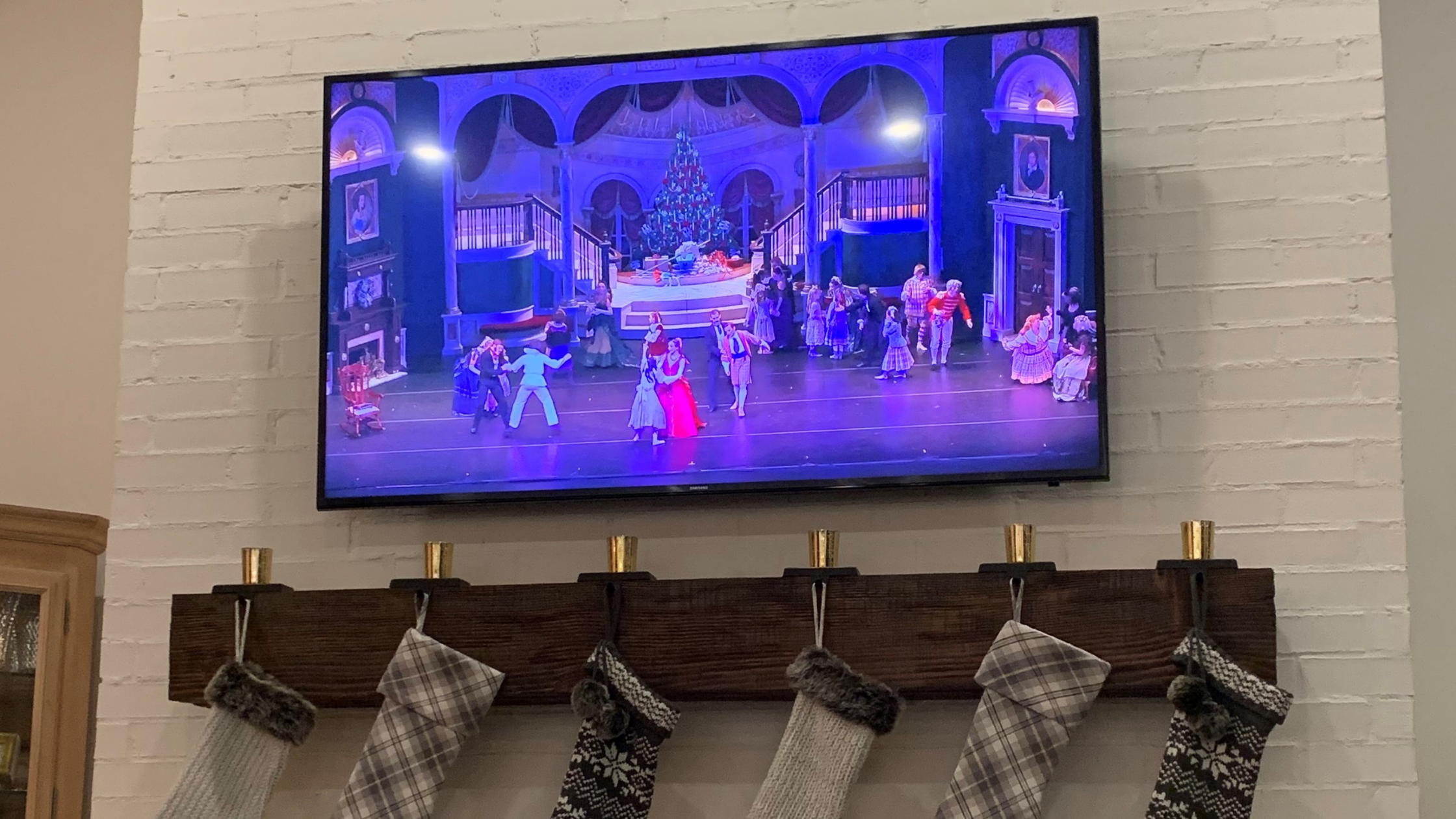 Act 1 of The Nutcracker playing on a TV hanging above a fireplace