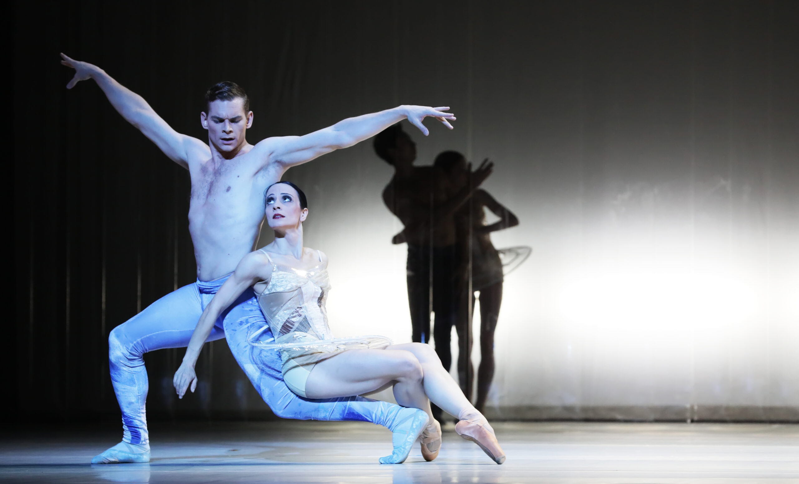 Male dancer wearing blue tights in a lunging position, with a female dancer in a nude-colored leotard and clear tutu resting against his supporting leg.